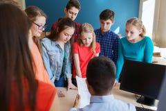 Grupo de estudiantes y de profesor con las pruebas en la escuela Imagenes de archivo