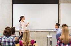 Grupo de estudiantes y de profesor sonriente en sala de clase Imágenes de archivo libres de regalías