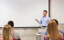 Grupo de estudiantes y de profesor sonriente en sala de clase Foto de archivo