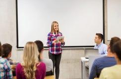 Grupo de estudiantes y de profesor sonrientes en sala de clase Foto de archivo libre de regalías