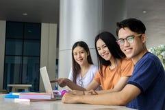 Grupo de estudiar asiático joven en la universidad que se sienta durante lectu Fotos de archivo libres de regalías