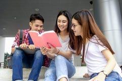 Grupo de estudiar asiático joven en la universidad que se sienta durante lectu Fotos de archivo