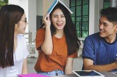 Grupo de estudiar asiático joven en la universidad que se sienta durante lectu Imagenes de archivo