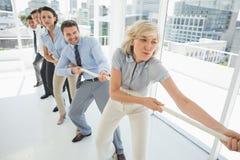 Grupo de executivos de corda puxando no escritório imagens de stock