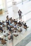 Grupo de executivos diversos que levantam suas mãos para fazer perguntas ao homem de negócios na conferência imagens de stock