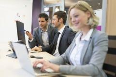 Grupo de executivos em um escritório moderno, trabalhando no computador Fotografia de Stock Royalty Free