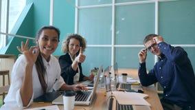 Grupo de executivos novos da raça misturada que mostram os polegares acima no escritório Conceito detrabalho Start-up 4K video estoque