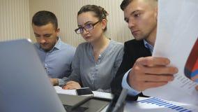 Grupo de executivos novos que sentam-se na tabela no escrit?rio moderno e que trabalham no projeto novo Dos colegas revis?o com c vídeos de arquivo