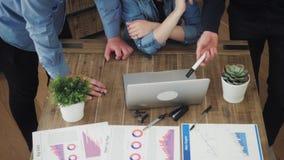Grupo de executivos novos que trabalham e que comunicam-se na mesa de escritório que olha o laptop vídeos de arquivo
