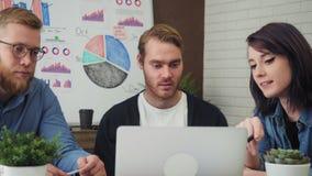 Grupo de executivos novos que trabalham e que comunicam-se na mesa de escritório que olha o laptop filme