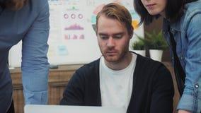 Grupo de executivos novos que trabalham e que comunicam-se na mesa de escritório que olha o laptop video estoque