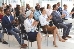 Grupo de executivos que aplaudem durante o seminário do negócio foto de stock