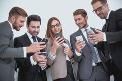 Grupo de executivos que leem uma mensagem em telefones fotos de stock