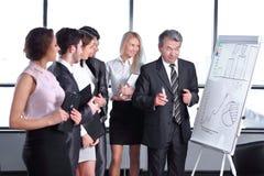 Grupo de executivos que olham o gr?fico no flipchart fotos de stock