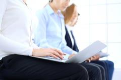 Grupo de executivos que sentam-se na entrevista de trabalho de espera do escritório, close-up Mãos da mulher que trabalham no por fotos de stock