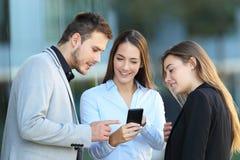 Grupo de executivos que usam um telefone na rua Foto de Stock Royalty Free