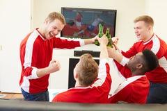 Grupo de fãs de esportes que olham o jogo na tevê em casa Imagens de Stock