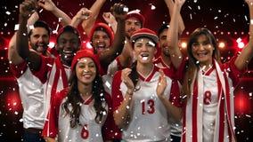 Grupo de fãs que cheering para sua equipe com confetes filme