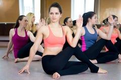 Grupo de fêmeas do iogue na pose de Ardha Matsyendrasana fotografia de stock