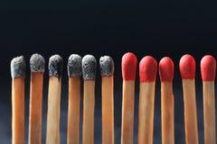 Grupo de fósforos queimados entre outros Fotografia de Stock Royalty Free