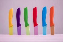 Grupo de facas de cozinha coloridas sobre o fundo cor-de-rosa Fotos de Stock Royalty Free