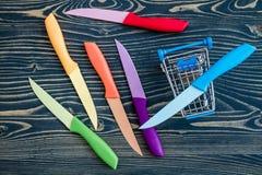 Grupo de facas de cozinha coloridas sobre o fundo de madeira azul Imagem de Stock