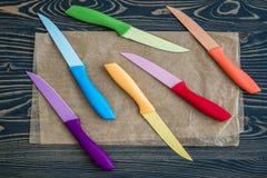 Grupo de facas de cozinha coloridas sobre o fundo de madeira azul Fotos de Stock