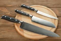 Grupo de facas de cozinha e de placa de corte Fotografia de Stock Royalty Free