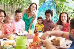 Grupo de famílias que apreciam a refeição exterior em casa imagens de stock royalty free