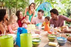 Grupo de famílias que comemoram o aniversário da criança em casa fotos de stock royalty free