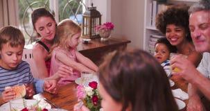 Grupo de famílias que têm a refeição em casa junto video estoque