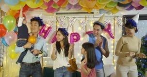 Grupo de familia asiática joven que baila junto en evento del partido en casa metrajes