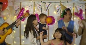 Grupo de familia asiática joven que baila junto en evento del partido en casa almacen de metraje de vídeo