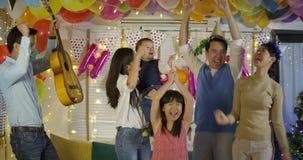 Grupo de familia asiática joven que baila junto en evento del partido en casa almacen de video