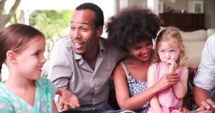 Grupo de familias en casa en patio que habla junto almacen de metraje de vídeo