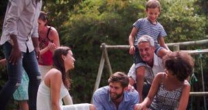 Grupo de familias que juegan en jardín junto almacen de metraje de vídeo