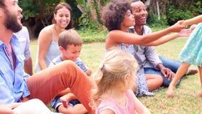 Grupo de familias que juegan en jardín junto almacen de video