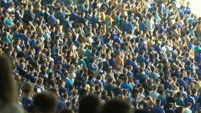 Grupo de fanáticos del fútbol que aplauden y que cantan en el estadio de la manera organizada almacen de metraje de vídeo