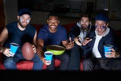 Grupo de fans de deportes masculinos que miran el juego en la televisión Imagen de archivo libre de regalías