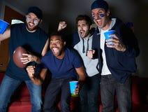 Grupo de fans de deportes masculinos que miran el juego en la televisión Imágenes de archivo libres de regalías