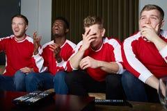 Grupo de fans de deportes que miran el juego en la TV en casa fotografía de archivo