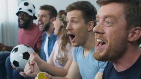 Grupo de fans que miran fútbol en la televisión en casa, entretenimiento conveniente metrajes