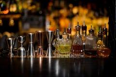 Grupo de ferramentas do empregado de bar que incluem jiggers e garrafas pequenas com li foto de stock royalty free