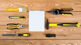 Grupo de ferramentas e de bloco de notas da mão em um fundo de madeira Fotografia de Stock Royalty Free