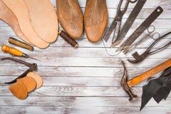 Grupo de ferramentas para o sapateiro no fundo de madeira branco Copie o espaço fotografia de stock