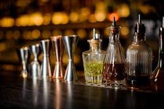 Grupo de ferramentas profissionais do empregado de bar que incluem jiggers e garrafas pequenas com licor imagens de stock