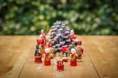 Grupo de figuras do Natal em torno de um pinecone Foto de Stock Royalty Free