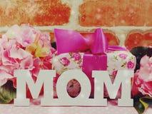 Grupo de flores com um fundo do dia do ` s da mãe da caixa de presente e da mamã da palavra Imagem de Stock