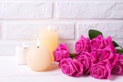 Grupo de flores cor-de-rosa das rosas e de três velas ardentes no whit Fotos de Stock Royalty Free