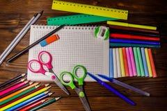 Grupo de fontes dos artigos de papelaria da escola na mesa de madeira De volta ao conceito da escola imagem de stock